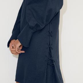 Denne behagelige kjole i rynket bomuld kan bruges som minikjole eller tunika. Den er så enkel, at den kan bruges overalt, men har charmerende detaljer, som gør den helt speciel. Den har påsyet bånd i siderne, som gradvist bliver mere løse, hvilket tilfører en fræk og afslappet stil til den ellers rene silhuet. Påsyet bånd ned ad siderne Lille bånd ved manchetterne. Materiale: 99% bomuld, 1% elastan. Mål str. 32: bryst 49cm, længde 83cm, ærmelængde 59cm.