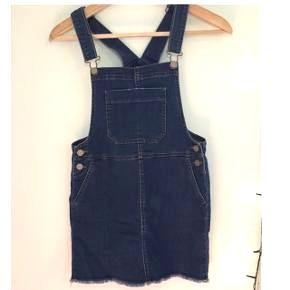 En overalls kjole i blå. Den er fra en butik i USA der hedder C&A. Den har spaltede spidser i bunden, hvilket er meningen.