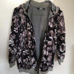 En fed overgangsjakke fra Molo med lommer og lynlås. Hætten kan klikkes af og på. Brugt få gange.