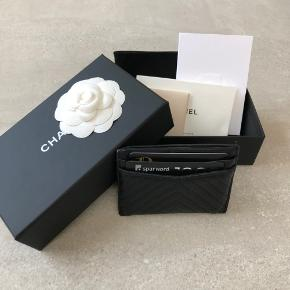 Smukkeste tidsløse klassiske Chanel Model 'So Black Chevron' fra 2016 Sort læder og sort logo Kortholder / Card Holder / Pung Udsolgt og meget sjælden Lambskin / lammeskind  Eneste af denne model til salg i EU.  Salgsprisen på markedet ligger på cirka 3.500-4.000 kr., men jeg sælger dog billigere grundet standen.  Alt medfølger, herunder kvittering, authenticity card, dustbag, æske og booklet.  Kortholderen bærer tydelige tegn af brug med mange kort, hvilket dog ikke ses når der er kort i.
