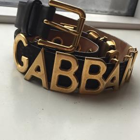 """Sælger dette gamle Dolce & Gabbana bælte da det bare har ligget og samlet støv de sidste 10-12 år...  Af logiske årsager og alderen taget i betratning, så har bæltet lidt brugsspor fra tidens løb :-)  Bæltet har dog stadig masser af år tilbage i sig, og de er et sjældent syn efterhånden.  Længde: 106cm Bredde: 3cm  Bæltet er brunt med guld-bogstaver, som """"skøjter"""" frem og tilbage.  Tænker at der må være nogen derude, som kan have gavn af det.  Kom med et bud."""