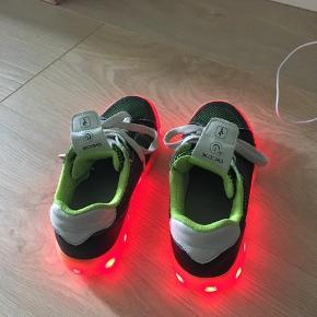 Den kan også lyse og blinke i andre farver og usb opladeren til skoene følger med.