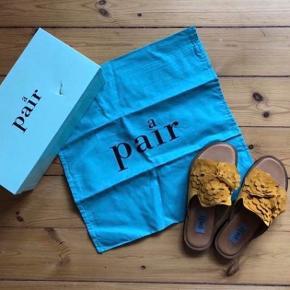 Sødeste flade slippers / klipklapper sandaler i karry gul ruskind med skindfoer og små blomster. Super fine til sommer og sol eller til dine glimmer strømpebukser. De er kun blevet prøvet på, bliver solgt med æske og pose.