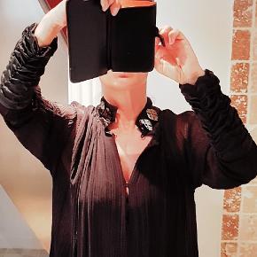 💮 MUNTHE PLUS SIMONSEN Silkekjole. (Her brugt med sort underkjole, medfølger ikke) Jeg har fjernet materiale- og str mærket, da det kunne ses igennem.  Manchetter og krave i ren glatvævet silke. Selve kjolen i chiffon- vævning  - også ren silke, som jeg husker det. Str L passer 40 - 42. Husker ikke nøjagtige str, men jeg er en 38/40 164cm høj og den er lige lidt for stor til mig desværre over skulderen.  Den har skjult knaplukning, kan bruges åben og lukket i halsen. Det sølvfarvede pynt på kraven kan nemt fjernes, hvis det er. - Er blot hæftet på med få sting.  Standen er næsten som ny. Købt i Second hand shop til 300,-  (Selve Munthe + mærket i nakken har et lille hak) Længde fra øverst på skulder ca 92 - 93cm