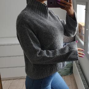 Flot grå sweater med høj hals Str small  Den er brugt et par gange, fremstår flot. Den har lidt vaskeslid i stoffet, men fremstår ellers pænt  jeg er 171cm høj Den sælges for 300kr eller 340kr inkl fragt med DAO