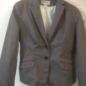 Mærke: H&M Størrelse: 38 farve: Brunlig farve.  Stoffet : glat og en anelse blankt Materiale: 97 % cotton og 3% elastan. Foret er polyester og viscose Stand: Aldrig brugt  Sælges 75 kr