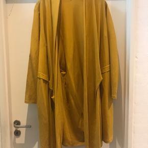 Smart drape cardigan i karry farvet med spc detalje / syninger og den har lommer .  Kun brugt 1-2 gange .  Str L ( 50-52 )  Ny pris 800 kr