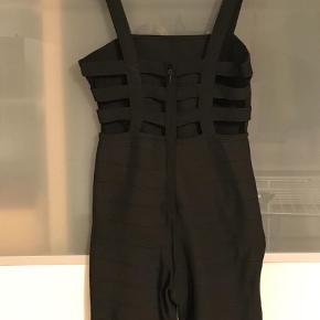 """Varetype: Jumpsuit Størrelse: S Farve: Sort  Cool, sexet jumpsuit i bandagestof. Jeg mener, den er fra Zara, men har åbenbart klippet mærket ud - det har nok kradset, da den sidder meget tæt til kroppen. Aldrig gået med - kun prøvet på. Sælges, da jeg må sande, at jeg ikke kommer til at bruge den.  Den er åben i """"striber"""" på en superflot måde henover ryggen (se billede) og heldækkende foran. Sender gerne flere billeder :-)  Porto er et skøn - pris afhænger af købets forsendelsesvalg. Man er også meget velkommen til at afhente og prøve før køb."""