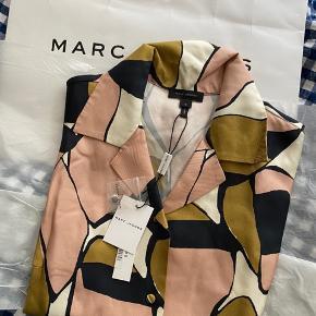 """Jeg overvejer at sælge denne smukke silkeskjorte fra Marc Jacobs, skjorten er helt ny med prismærke og er kun prøvet på, sælges, da jeg har så meget tøj. Falder smukt pga. den """"tunge"""" silke. Kommer fra et ikke ryger hjem og ikke dyre hjem. Skjorten er 100% silke.  Jeg bytter ikke, respekter venligst dette. Samtidig betaler køber gebyr ved tshandel (sælger og køber)   Mål: Skulder: 44 cm"""