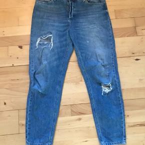 Mom jeans med Ripped på begge bukseben. Lommer foran og bagpå.