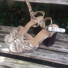 Højhælet sandal. Gode at gå i. Den ene hæl har en lille plet, hvor 'træet' er røget af. Ellers så er der nogle skrammer på begge hæle.