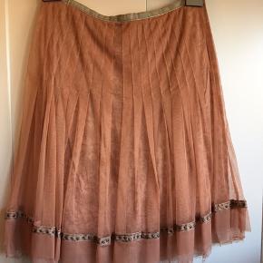 Feminin nederdel med mange fine detaljer.  Tyl yderst, bomuld inderst, velourbånd i taljen.  Flere billeder kan sendes.