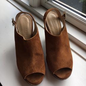 Flotte pleateau sko fra Gardenia i brun ruskind. Højde 11 cm. Kun brugt 2 gange, så fremstår næsten som nye