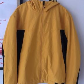 Gul jakke fra Jack & Jones. Skulle være regn og vindtæt, men det er altså ikke de helt store regnskyl den kan klare. Kunne være en god løbejakke eller overgangsjakke.  Køb én vare og få en valgfri af mine varer til 50 kr. med i købet :)