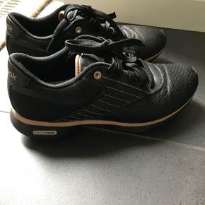Easy tone Sneakers fra Reebok i sort og guld farve..Ergonomisk sål så de er utrolig behagelige at gå i😀 Brugt 3 gange.. MEGET pæn stand..