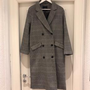 Elegant, ternet, oversized jakke fra Monki. Jakken lukkes med tre sorte knapper fortil og en enkelt usynlig knap inderst. Jakken har to dybe lommer fortil.  Sælges da jeg desværre ikke kan passe den.   Jeg bytter ikke 😊