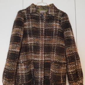 Fin frakke med lysegrønt for og plissering på ryggen. Løs i formenLavet i akryl og uld.