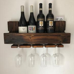 Smukke håndlavede vinhylder af træ fra halvpaller.  Nr på hylde fremgår af hvid seddel til højre på fotos.  Plads til 4 flasker og 4 glas (Mål: B:60cm, H:26cm)  Slebet, brændt og olieret med flot gyldent skær.   Hænges op via 2 huller i bagerste bræt. Skruer og dybler til montering inkluderet.  Nedenfor link til fotos af alle vinhylder med og uden flasker/glas:  https://fotobox.dk/vinhylde/3684-3f6df2af2a8a1210801c5b1851f1eaa3  Fragt: Afhentning gratis, GLS pakkeshop (hele landet) 75kr.  Kontant ved afhentning, bankoverførsel eller paypal ved forsendelse.
