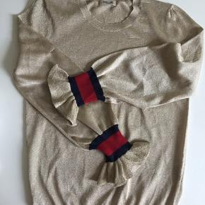 Super guld lurex sweater med kontrast rib vwd ærme.  Der er nogle få tråde trukket. Se på billed nr 2.  Bluse var udsalg næsten med det samme.