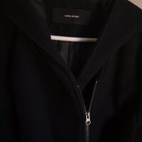 Overgangsjakke frakke med hætte samt bindebånd i taljen. Foret. Lukkes med lynlås. Størrelsen passer bedst en 42 evt. 40-44, den er lidt til den lille side.  Jakken har været brugt, men er i pæn stand bortset fra en syning, der er gået op ved lommen, se venligst foto 9. OBS jakken har været i nærheden af hund.  Jakken må ikke vaskes, men kan renses. Dette kan den måske trænge til, men ellers er den fin, og rigtig god til efteråret.   165,- + fragt med Dao kr. 37,-  Bytter ikke.