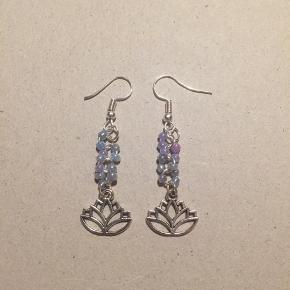 Håndlavede øreringe med lotus vedhæng og lyselilla glasperler, der reflekterer smukt!  Andre versioner på min profil 💕