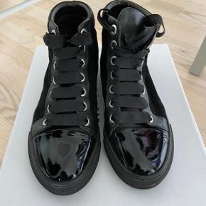 Fed sneakers ankelstøvle i lækker kvalitet fra Billi Bi i trendy design. Sort ruskind/skind med lakdetalje og satinsnørebånd. Fin stand.