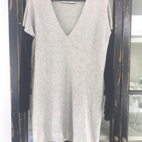 Lækker blød strik kjole fra Marlene Birger. Lys grå med sorte ærmer.