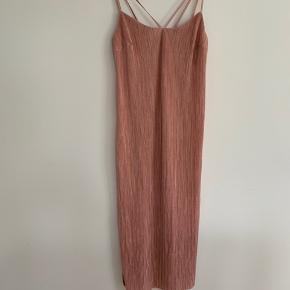 Elegant, nudefarvet kjole med slids og smuk strop-detalje. 🌸 Sælges grundet flytning. 🌸 Str. M 🌸 Køber betaler porto.