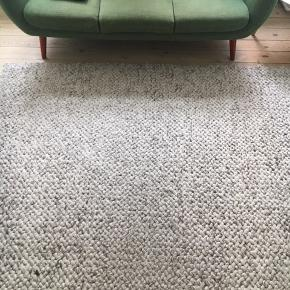 Flot gulvtæppe i uld fra Bolia. Ca. 180cm * 250cm. Der er en lille plet, som ses på billedet. Det er neglelak, som formodentlig kan fjernes med neglelakfjerner. Man kan også sætte en sofa eller stol over pletten