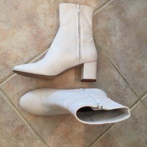 Nypris: 499 kr Materiale: Læder Hæl: 6 cm Levering er inkl. i prisen.   Skoene er imprægneret og har aldrig været brugt. Skoenes slidsåler er dog blevet renset med en børste som har ridset dem - hælene og selve læderet har ingen brugstegn. Dertil er der en lille misfarvet firkant under den venstre sko, som er resterne af prismærket.