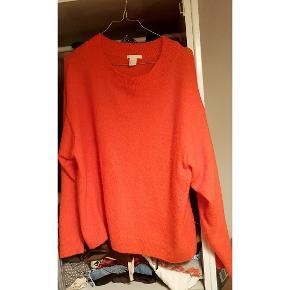 Stærk orange sweater der er super blød og behagelig ar have på.  3% Uld 6% Elastan 52% akryl 27% polyamide 12% polyester