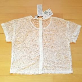 Hvid T-shirt med blonder og knapper bagpå Gennemsigtig blondetop Str. M Har knapper bagpå Aldrig brugt Stadig med prismærke Jeg har den også i sort