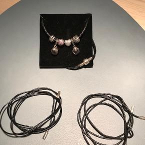 2 x sort tyndt lædersnor m. pandora logo ( et nyt/et brugt)  1 x flettet læderarmbånd  6 x vedhæng  Fremstår som nyt ( m. undt af den ene lædersnor)