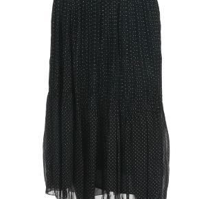 Super fed nederdel i str 38. Sort med hvide små prikker. Er i to lag. 100 % polyester