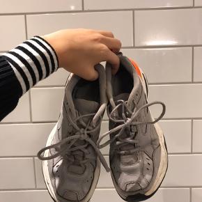 Nike M2K tekno, i grå og orange. De er brug en del og har nogle hakker i sålen. fremstår dog stadig pæne efter en vask.