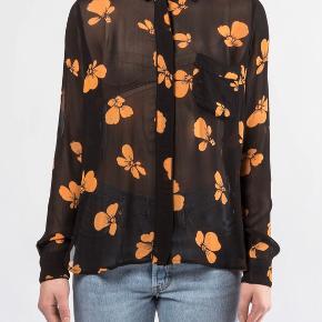 Jeg sælger min fine Ganni skjorte. Den er i 100 % viskose.  Den er brugt nogle gange og har nogle små tegn på slid, som blandt andet kan ses på 3. billede. Der er ikke noget, som man ser ved brug, men der er flere små præg af slid på skjorten.  Skjorten er str. 40, men vil anbefale en str. 38/40.   Skriv gerne, hvis du vil se flere billeder, mål eller andet.