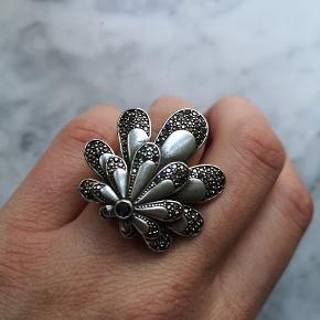 Flot stor justerbar ring i sølvbelægning og sorte sten. Belægningen er list slidt, men mest bagpå. Ingen sten mangler.