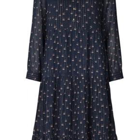 Smuk kjole med fint print af blomster og tynd guldtråd. Længde lidt ned under knæene