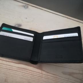 Ny, ubrugt sort Hugo Boss pung, i præget læder m. rum til kreditkort og sedler. Købt d. 4 august 2020, aldrig brugt.