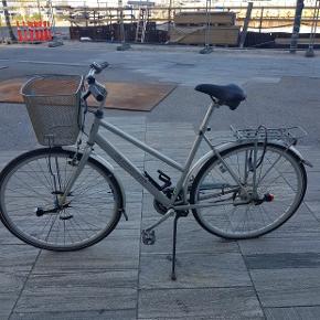 """Batavus damecykel i sølv.  Fin stand, kører som den skal. Stelstørrelse 54 cm og 28"""" hjul  Fladt baghjul som køber skal fikse. Lås følger ikke med."""