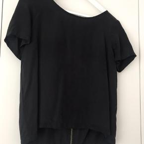 Sort pæn T-shirt i cupro-materiale som får den til at fremstå eksklusiv og lækker med fed lynlås på ryggen