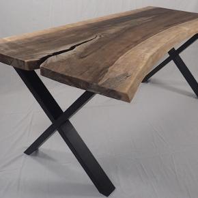 PLANKEBORD AF DANSK VALNØDDETRÆ. Bordet er massivt og snedkeret ud af én enkelt stamme. Det er nylavet og leder efter sit første hjem. Det måler 164cm i lang, 76 - 108 cm bred Stammen har sin oprindelse i Nordjylland og er blevet skåret op med en særligt bred klinge for at bevare den fulde og ret unikke bredde. Et virkelig udsøgt stykke træ. At lave borde er en hobby, til daglig er jeg tømrer. Bordet er derfor af høj kvalitet men til en billig pris, da jeg ikke er noget fancy firma. Så gør en god handel og køb dette top lækre bord til det halve af hvad tilsvarende kan købes til.