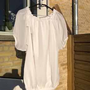 Super fin og feminin bluse med halvlange ærmer. Ærmerne er i gennemsigtigt stof, men selve blusen har en indertop i glat stof.   Der er elastik i bunden og bindebånd i udskæringen.   100% polyester.   Det er en str. 36 men kan sagtens bruges af en str. 38/M også.   Køber betaler evt porto. Jeg sender med Dao.