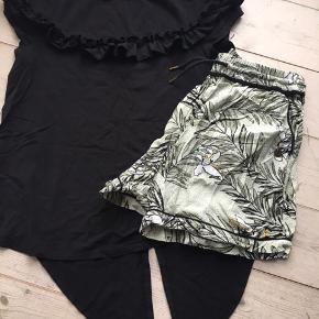 Skønt sommersæt med sort t-shirt der har pingvinhale - den kan hænge løs eller bindes til knude. Shortsene passer til sættet.   Jeg bytter ikke. 75 kr for sættet - prisen er fast.