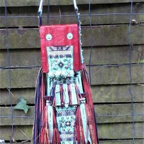 """Brand: Etnisk design - taske - pung - super dekorativt kunsthåndværk Varetype: Dekoration - tuareg taske pung - afrikansk nomade stamme Størrelse: 48 x 13 cm Farve: Multi Oprindelig købspris: 800 kr.  En super dekorativ taske pung i kamel skind . Kan bruges som det den er lavet til , eller et ophæng , der gir et godt blikfang . Har utallige detaljer , i mange forskellige teknikker , som bla er prægning , applikationer , broderi og påsatte dutter og snøre . Hele pungen / tasken måler ( uden tekstil snøre ) ca 48 x 13 cm . Opbevarings rummet måler 11 x 9,5 cm , med bræmme top , sider og bund , på godt 3,5 cm . Lukning med klap , som har en """" perle """" og snøre , til yderligere lukning . påsat snører som rem . Denne taske pung , har i modsætning til , min anden tuareg pung ( se annonce ) ikke været i brug , hos de beduin nomader der har skabt den ."""