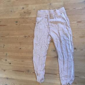 Beige bukser med hvide striber langs siderne 🐚  Fra H&M og en str. 34 - kan passes imellem str. 34-38.  Kan blive strøget inden afsendelse - så ser den så godt som ny ud.  OBS: jeg hverken bytter eller tager tøj retur igen.  Skriv gerne for mere information eller billeder!  Handler med DAO 🐚 Tager også imod seriøse bud. 🌟