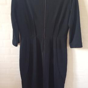 Så smuk og klassisk kjole fra In Wear. Slankende detaljer i talje og på hofter - satinkant i den bådformede halsudskæring samt bag på ved lynlås - virkelig en lækker kjole.