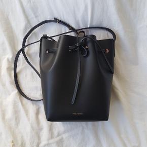 Mansur Gavriel Mini Bucket Bag i farven Black/Ballerina. Fremstillet i læder. Højde 25 cm, bredde 18 cm og dybde 12 cm.  Minimum længde skulderstrop er 100 cm og max længde er 118 cm, dette kan indstilles i 3 forskellige længder.  Købt fra MyTheresa 21.08.17 til 515 Euro.  Alt medfølger til tasken.  Brugt omkring 30 gange og har fået lidt ridser, men dette kan ikke undgås ved almindeligt brug.  Nypris mellem 3800 og 3900 kr. afhængig af kursen.   Jeg bytter ikke.