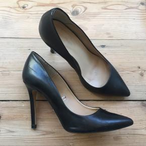 Klassiske sorte stilletter i ægte læder.  Læderet har løsnet sig en smule nederst på den ene hæl, men det kan næsten ikke ses - kan fikset på 2 sekunder hos en skomager. Se billeder.   Bytter ikke!:) men kom endelig med bud!   Afhentes på Christianshavn.