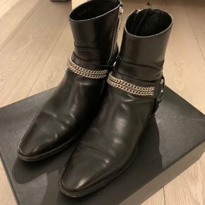 """Saint Laurent FW13 Chain Wyatts Leather Den mest anerkendte sæson i Hedi Slimane's tid som CD hos Saint Laurent. Disse støvler er mægtig sjældne fra denne sæson, da der er """"Exposed Zipper"""". De er størrrelse 39 men kan passe en 40-41 hvis man ik har for brede fødder. Det er damemodellen, dog ikke den store forskel fra mændenes. Billigste worldwide: 3500,- finder du dem aldrig nogensinde billigere til i denne stand. Boks og dustbag medfølger."""